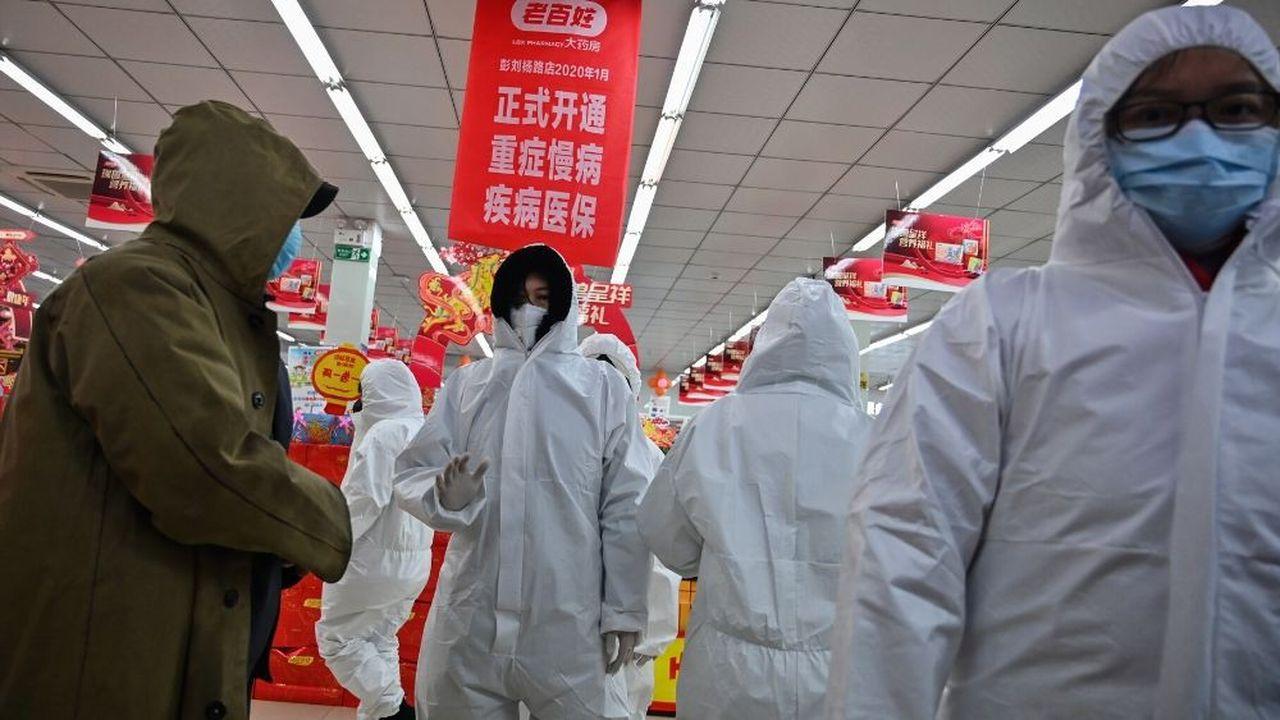 Les employés de Harmacy portant des vêtements et des masques de protection servent des clients samedi à Wuhan.