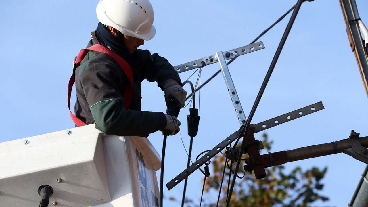 Un technicien de SNEF télécoms passe un câble de fibre optique dans une traverse.