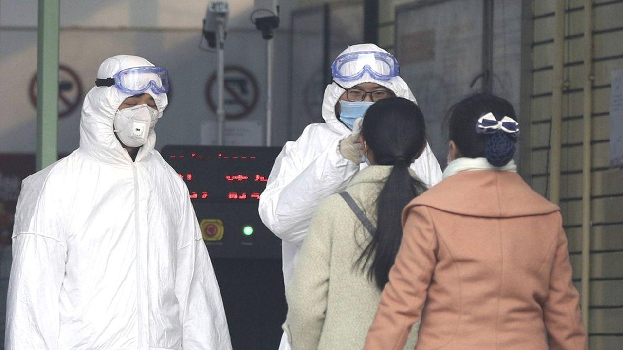 Des officiers de sécurité, en charge de la santé, prennent la température de passagers voulant entrer dans le métro de Pékin, le 28janvier 2020.