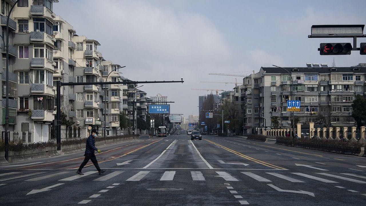 Un homme masqué traverse une avenue videdans la ville de Hangzhou, à 175 kilomètres de Shanghai, le 5février 2020.