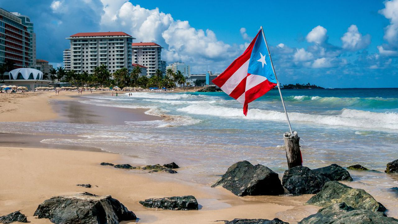A national flag flies over beautiful sunny day on a San Juan beach in January making for an excellent escape from the winter weather in New England.