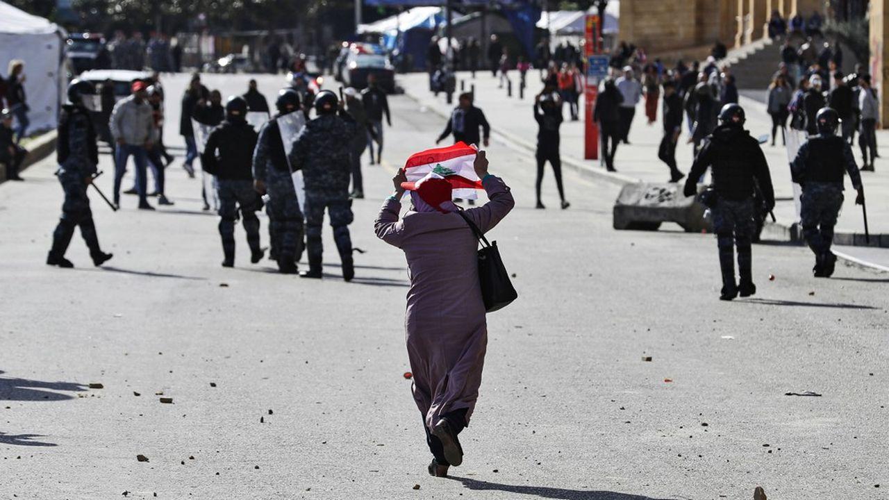 Une Libanaise brandit un drapeau devant des policiers lors d'une manifestaton d'opposants au gouvernement à Beyrouth, le 27janvier.