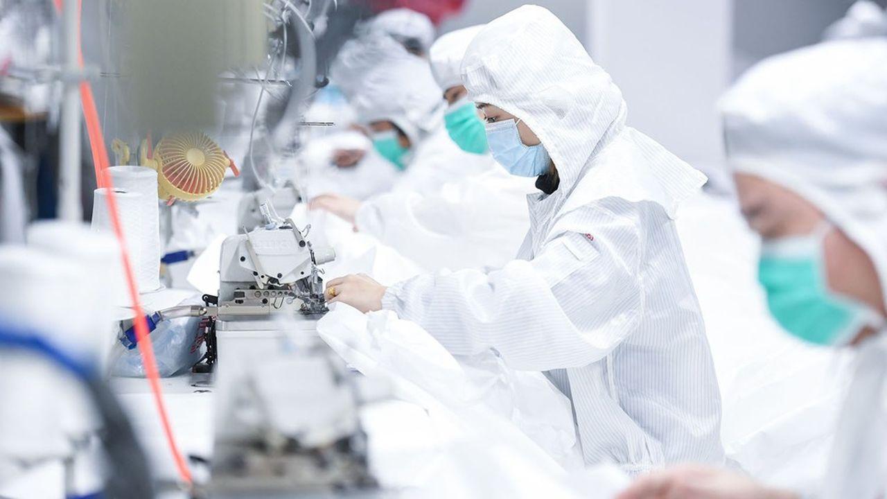 Dans une usine de mode à Shenzhen, les ouvriers sont contraints de travailler habillés de combinaisons de protection.