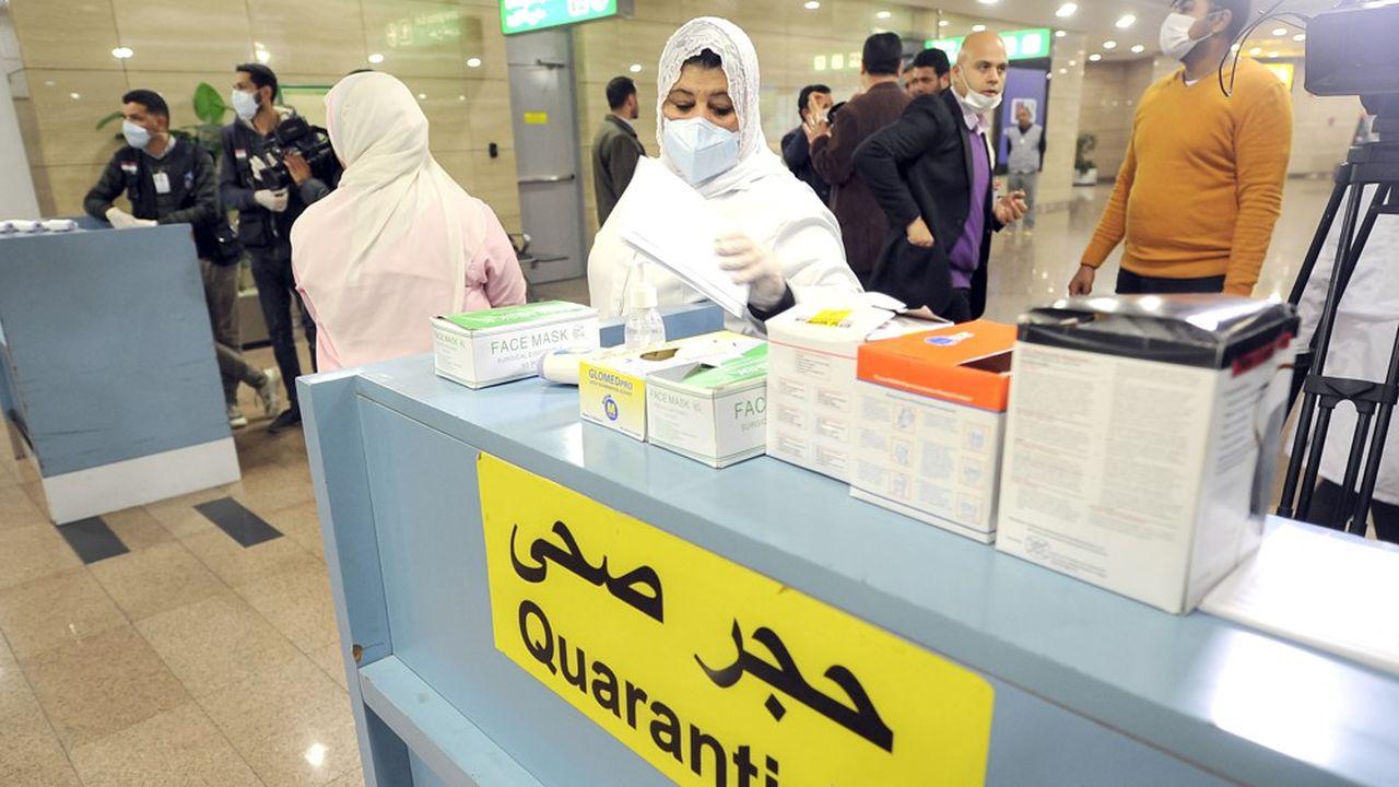 Des employés égyptiens se préparent à scanner la température des voyageurs arrivant à l'aéroport duCaire pour prévenir l'épidémie de coronavirus.