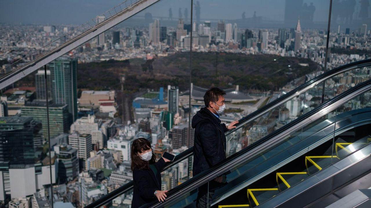 Deux Japonais portent des masques sur un Escalator à Tokyo. Le secteur du tourisme au Japon est particulièrement frappé par l'épidémie de coronavirus.