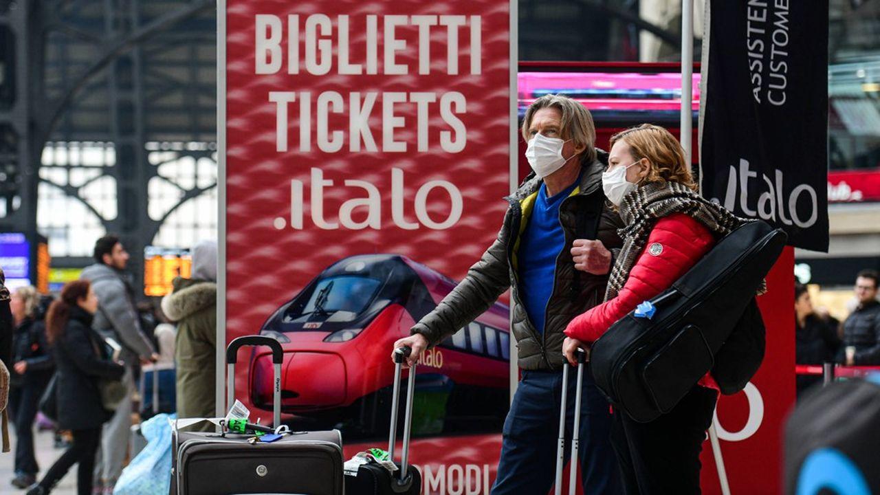 Des passagers portant des masques contre le coronavirus, à la gare centrale de Milan, en Italie.