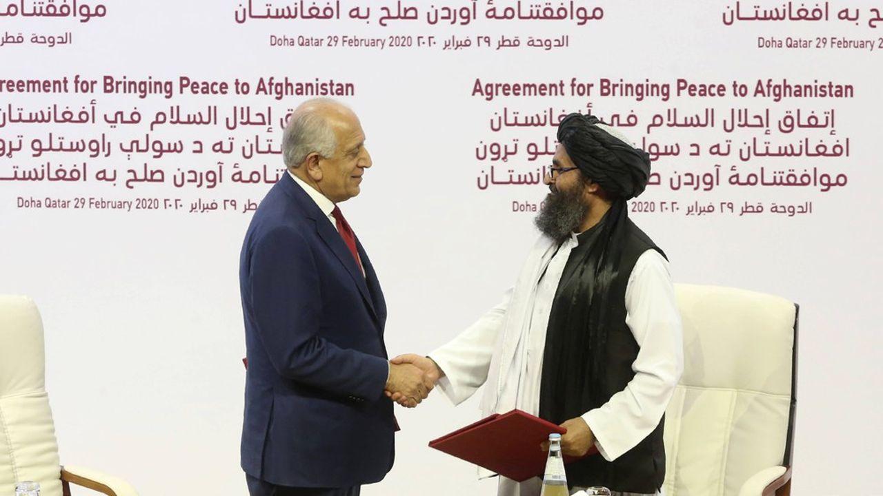 L'ambassadeur Zalmay Khalilzad pour les Etats-Unis (à gauche) et le mollah Abdul Ghani Baradar pour les talibans, se serrent la main après avoir signé samedi un accord à Doha (Qatar) ouvrant la voie au départ de l'armée américaine d'Afghanistan.
