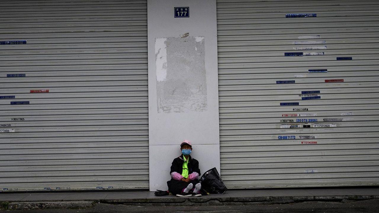 Un homme portant un masque assis devant les portes closes de l'atelier deZhejiang Xuda Shoes Co., une entreprise basée àWenzhou, en Chine.