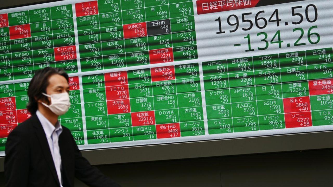 Un homme porte un masque en passant un tableau enregistrant les résultats de la Bourse de Tokyo.