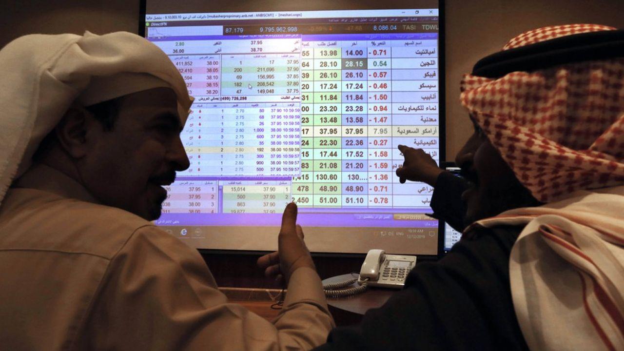 Des traders saoudiens suivent sur un écran des valeurs boursières à l'Arab National Bank, située àRiyad.