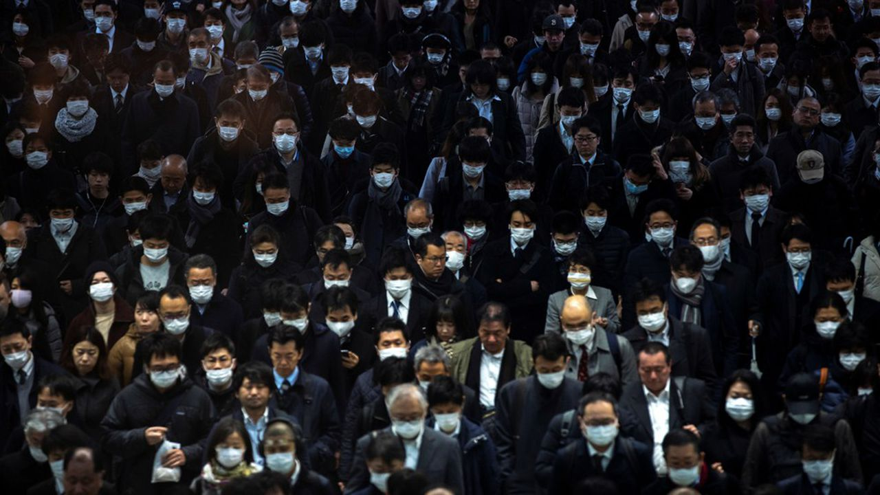 Des dizaines de Japonais, en gare de Shinagawa à Tokyo, portent un masque en cette période d'épidémie de coronavirus.