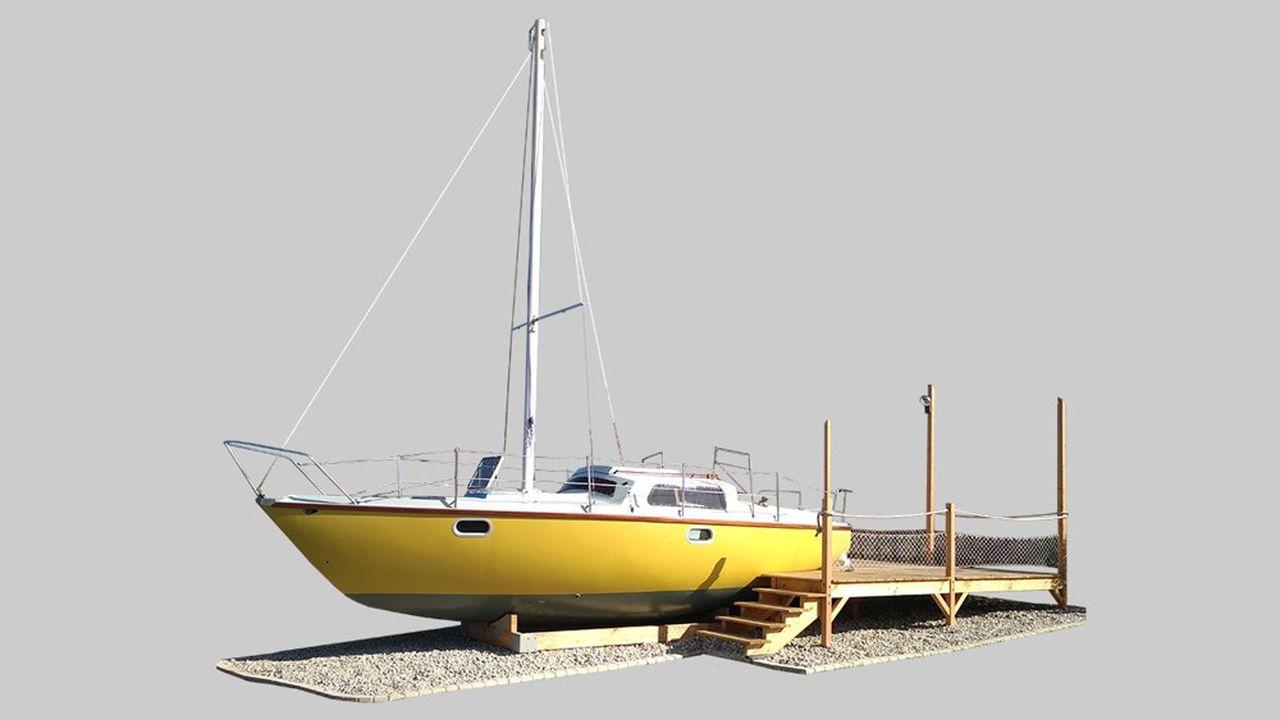 L'embarcation remise à neuf est posée à même le sol, tenue par un ber et agrémentée d'une terrasse en bois.