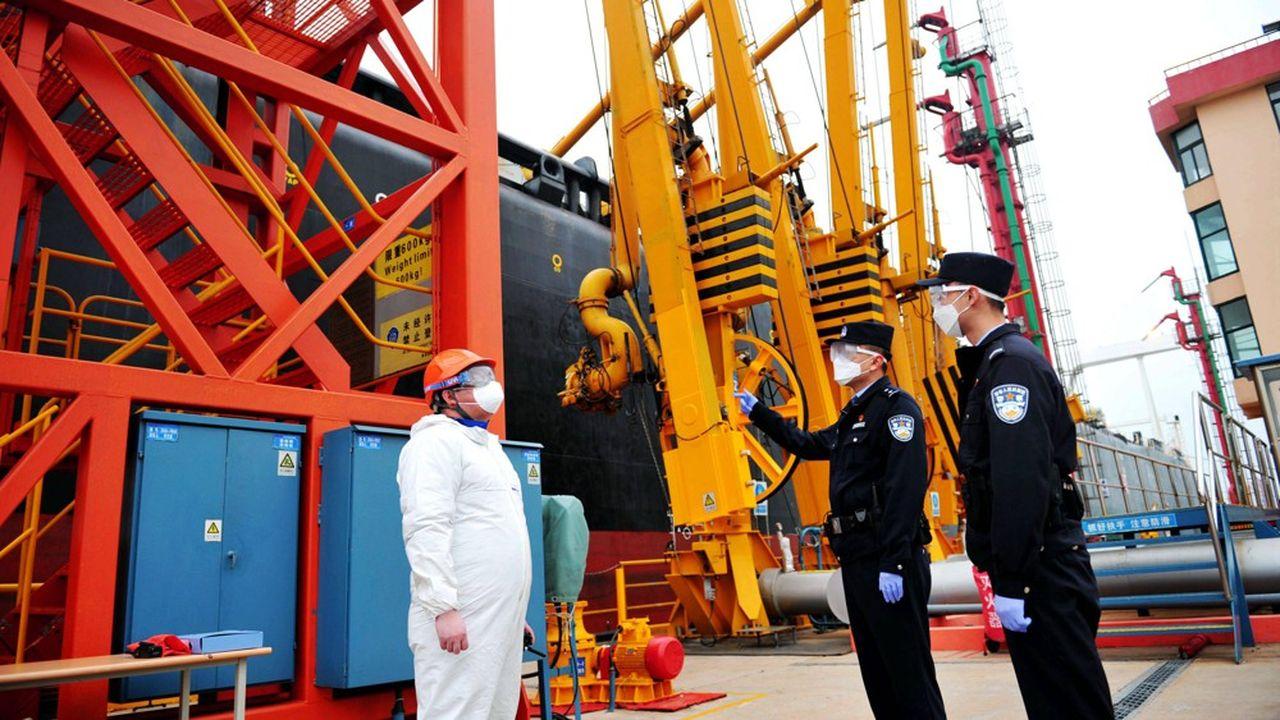 Les contrôles se renforcent à tous les postes-frontières aériens, terrestres et aussi portuaires comme lors du transfert de pétrole (notre photo) à Qingdao (Shandong).