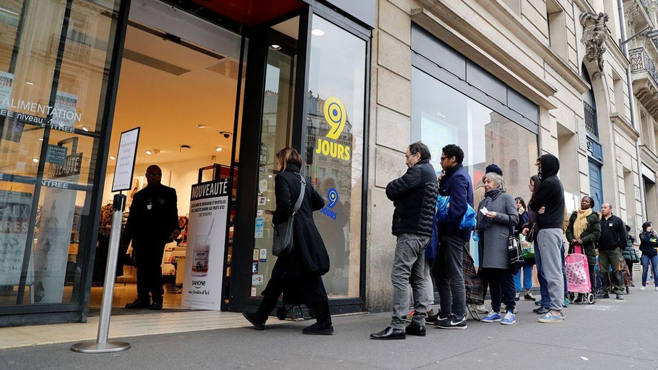 Les agents de sécurité doivent gérer les files d'attente devant les magasins pour maintenir les distances barrière.