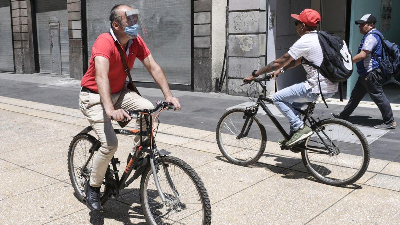 Un homme portant un masque circule à vélo dans les rues de Mexico, le 24mars.