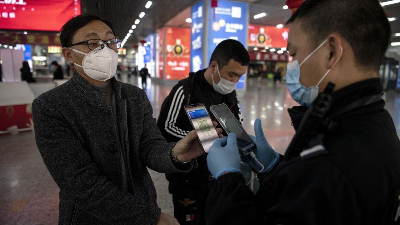Contrôle à la gare de Wenzhou (Chine) le 28 février. Pour pouvoir circuler, les passagers doivent montrer l'application Alipay Health Code, qui indique sous forme de QR Code le risque qu'ils aient été en contact avec le Covid-19. Seules les personnes dont le code est vert sont autorisées à se déplacer.