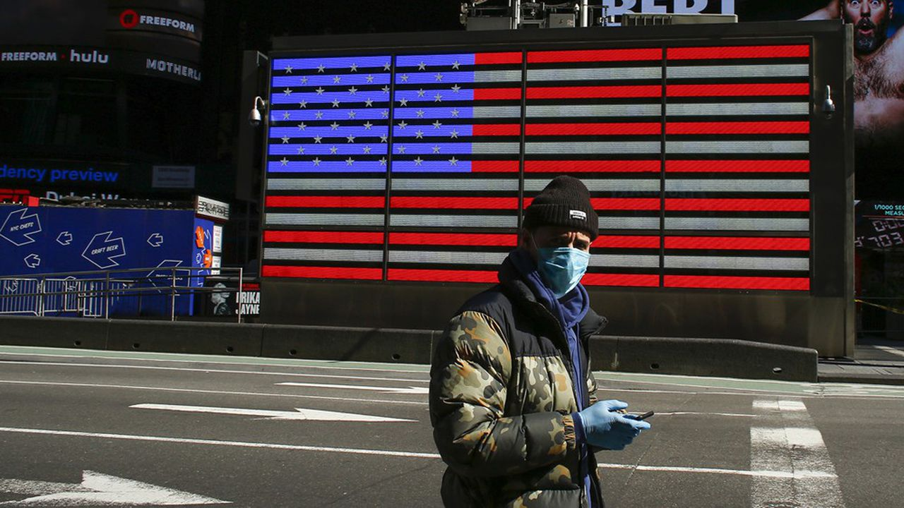 Un homme masqué dans un Times Square désert, à New York, le 22mars.
