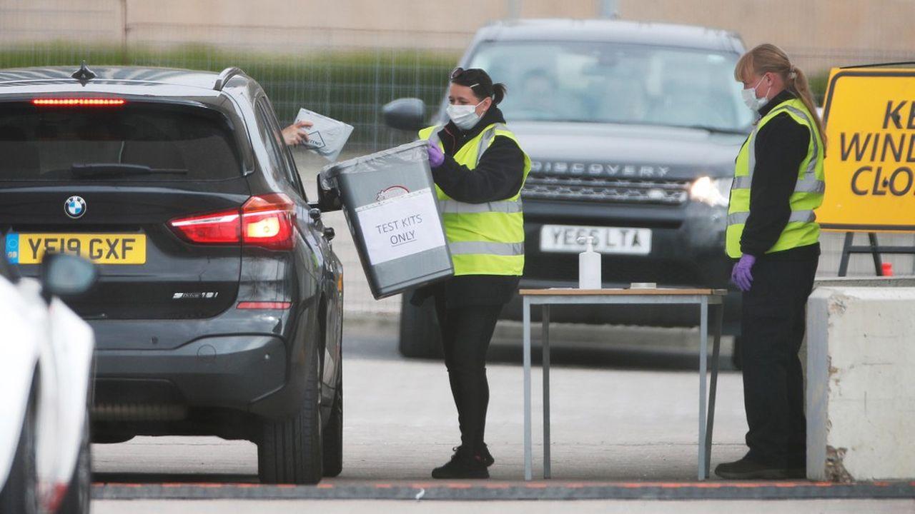 Des personnes testées remettent leurkit de test au personnel du centre de dépistage installé à l'O2 Arena, à Londres.