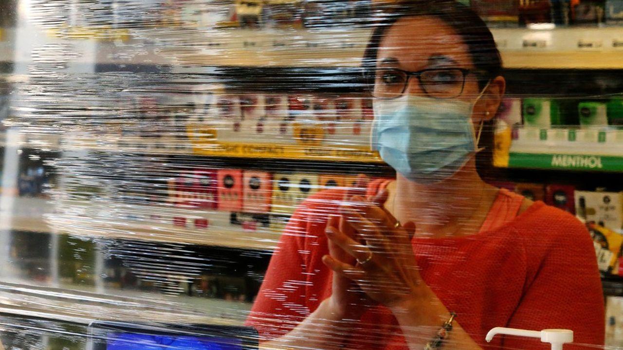 Une salariée d'un bar tabac à Reims porte un masque, le 25mars.