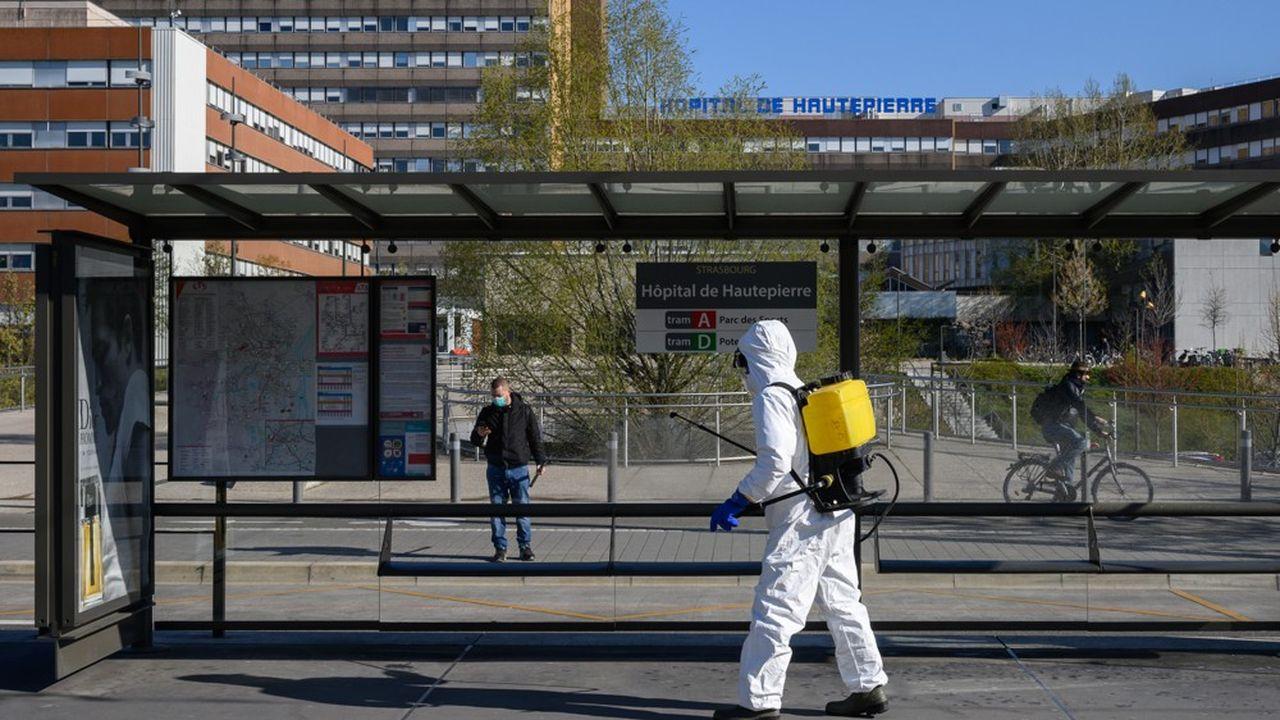 Un homme désinfecte la station de tram de l'hôpital de Strasbourg.
