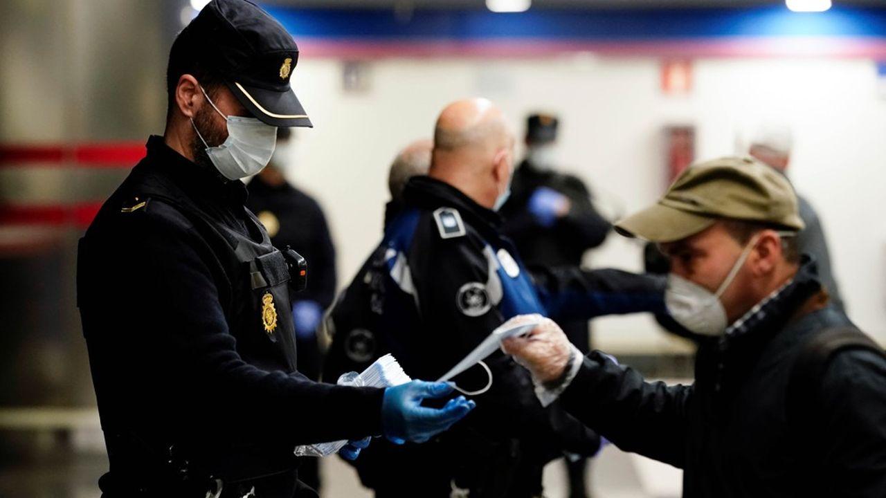 Un policier distribue des masques gratuits à la sortie d'une station de métro à Madrid, le 13avril 2020.