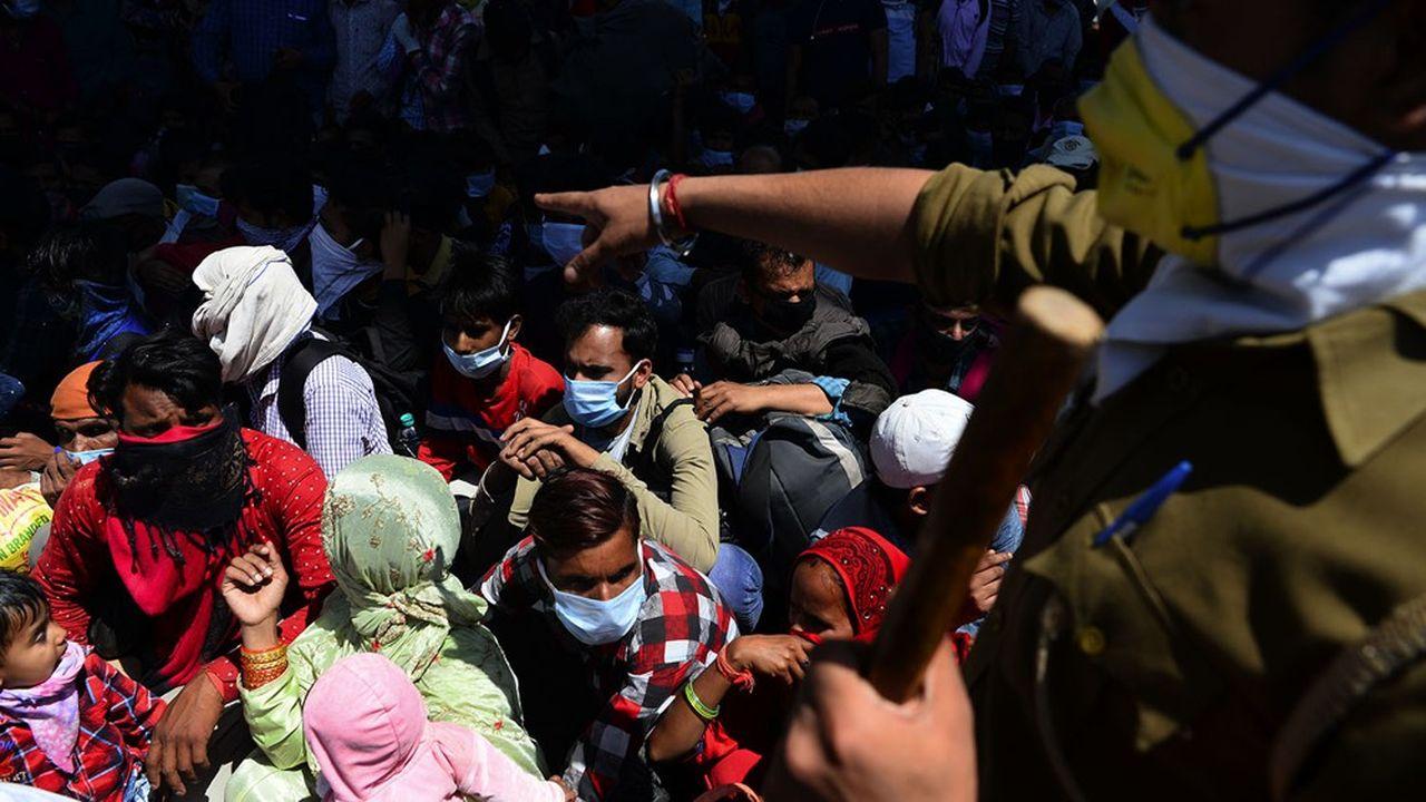 Un policier demande à des travailleurs migrants et leurs familles de se mettre enligne avant un départ en bus vers leurs villes d'origine finmars2020.