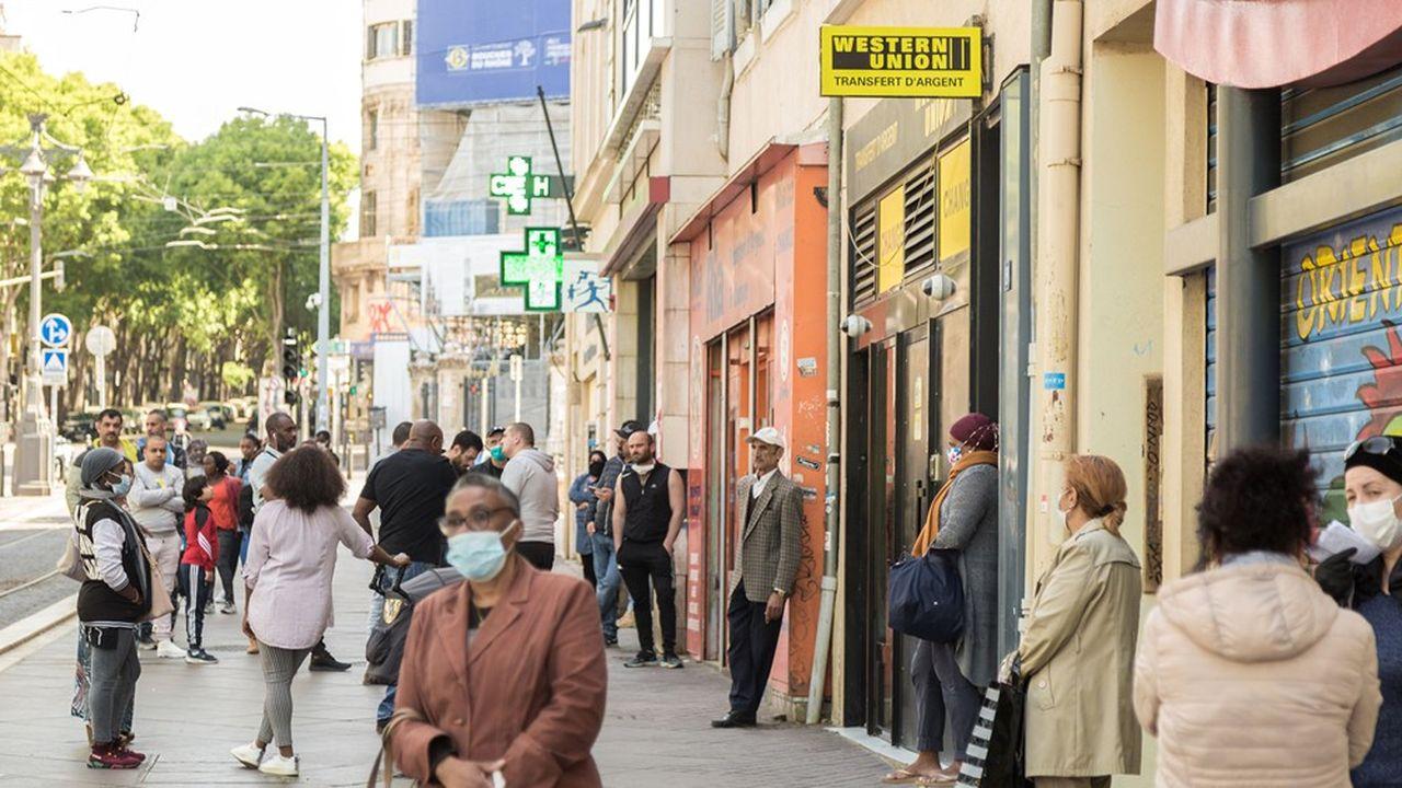 A Marseille, des personnes font la queue devant les bureaux d'une agence de transfert de fonds.