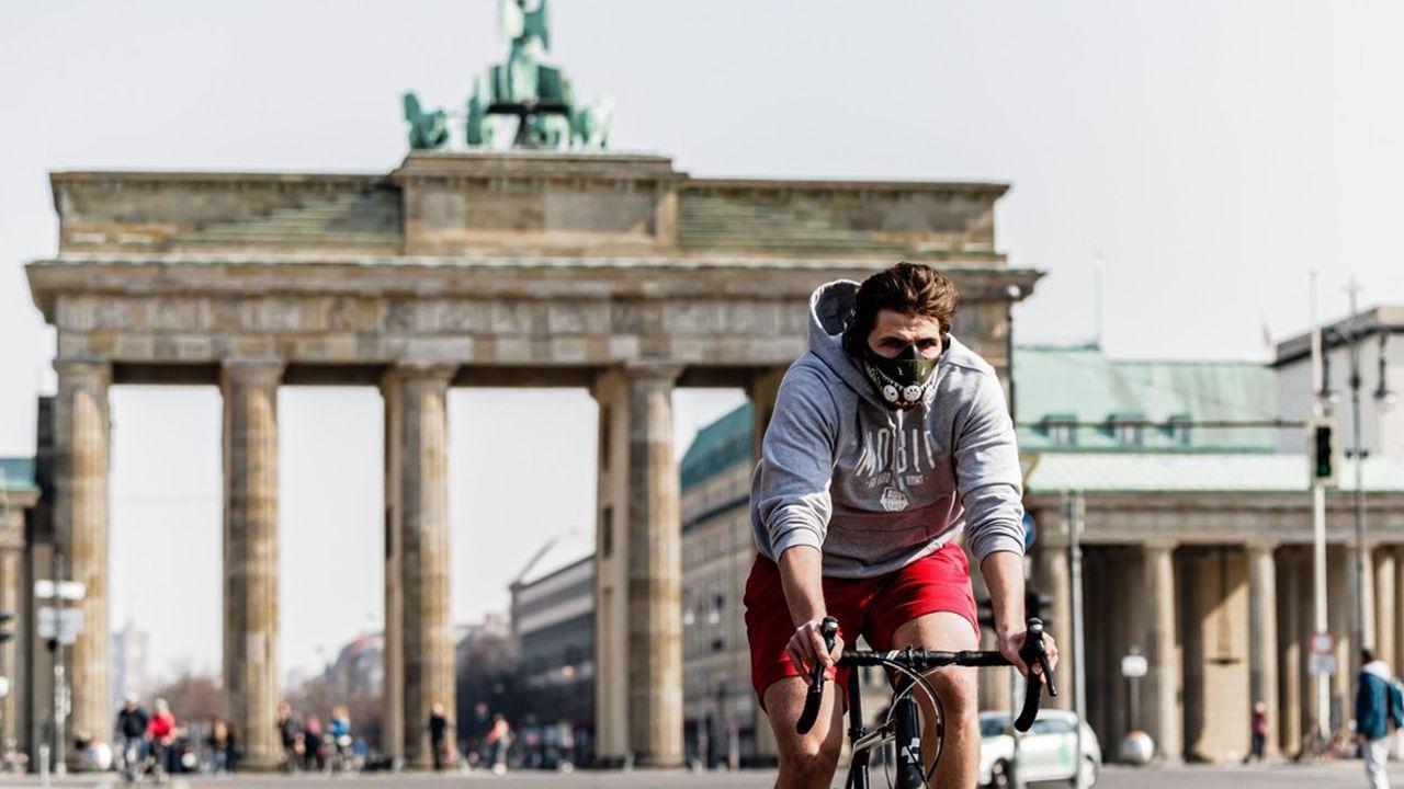 Un cycliste masqué devant la porte de Brandenburg à Berlin.