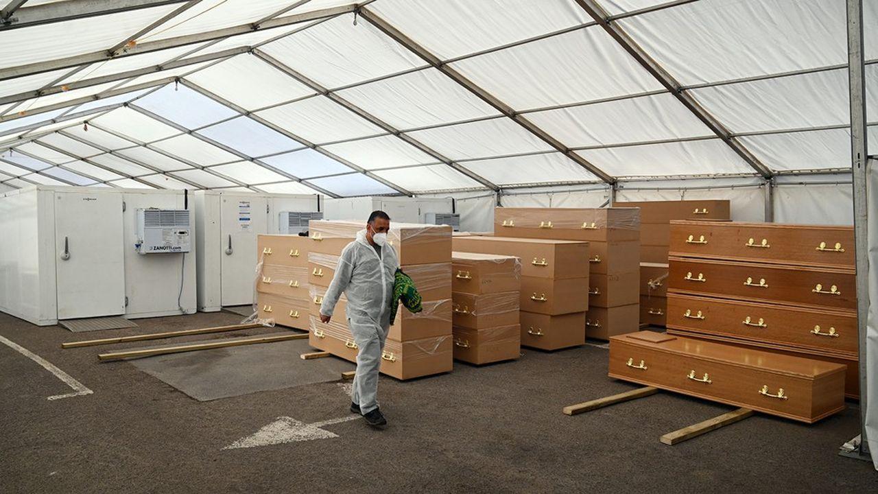Des cercueils sont stockés près de congélateurs dans un abri construit sur le parking de la mosquée centrale Jamia Mosque Ghamkol Sharif à Birmingham.