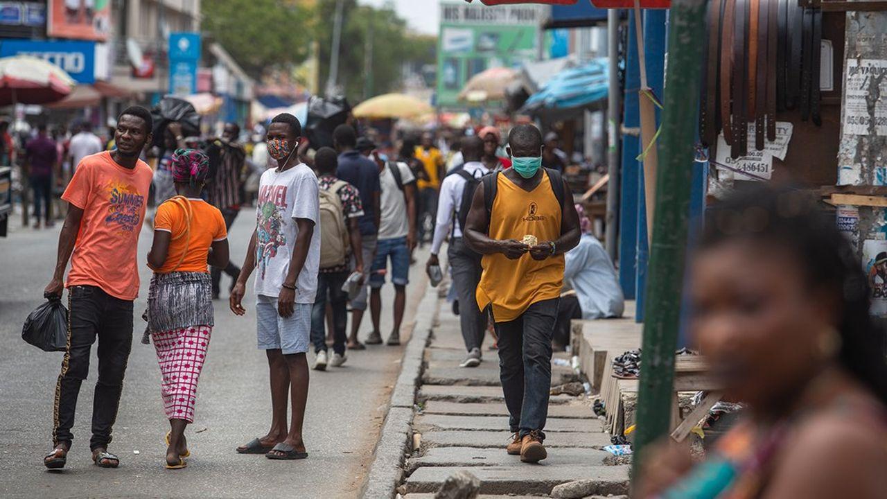 Les habitants portent un masque contre le Covid-19 dans les rues d'Accra, après que les mesures ont été allégées au Ghana, où les rues ont retrouvé de l'animation.