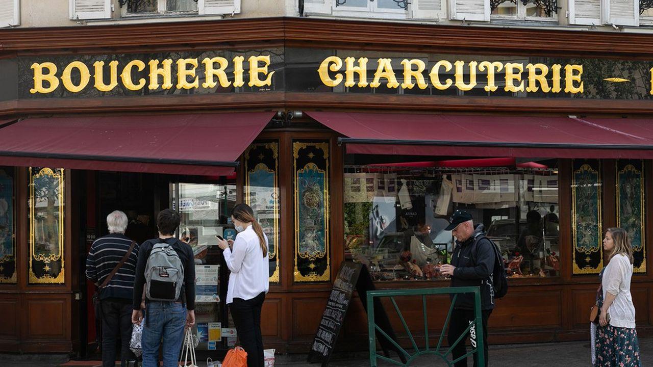 File d'attente de clients devant une triperie, boucherie, charcuterie, rôtisserie de centre-ville de Rueil-Malmaison dans les Hauts-de-Seine.