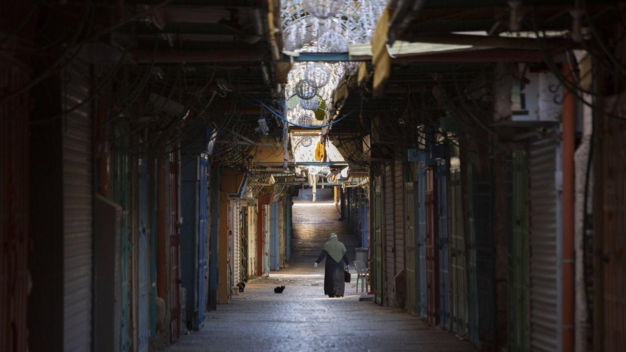 Une femme arpente les allées désertes du shouk de Jérusalem.