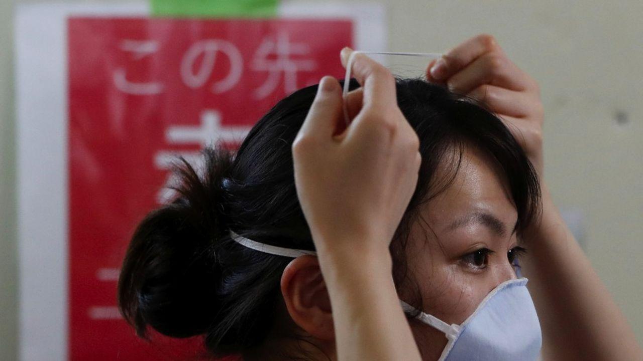 Une infirmière pose son masque dans un service de réanimation dédié au Covid-19 à St. Marianna Medical University Hospital à Kawasaki, au sud de Tokyo, le 4mai 2020.