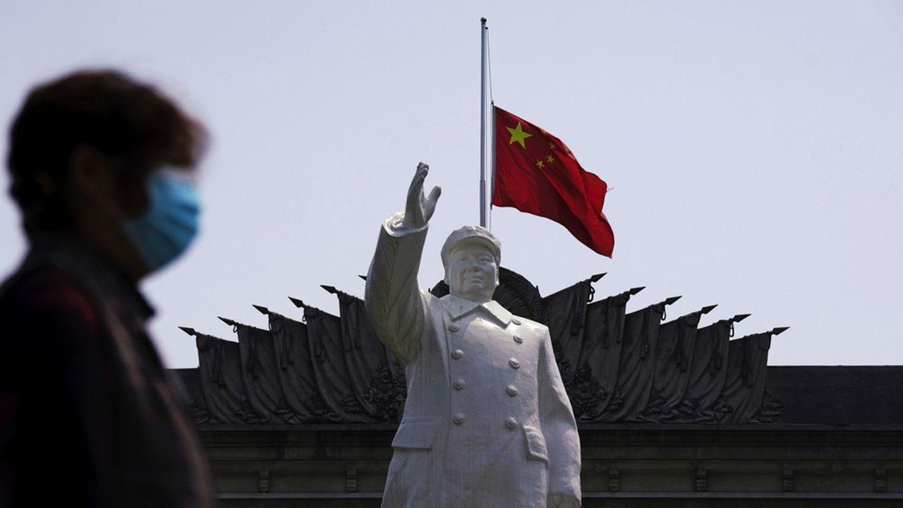 Le drapeau chinois à mi-mât derrière une statue de Mao à Wuhan.