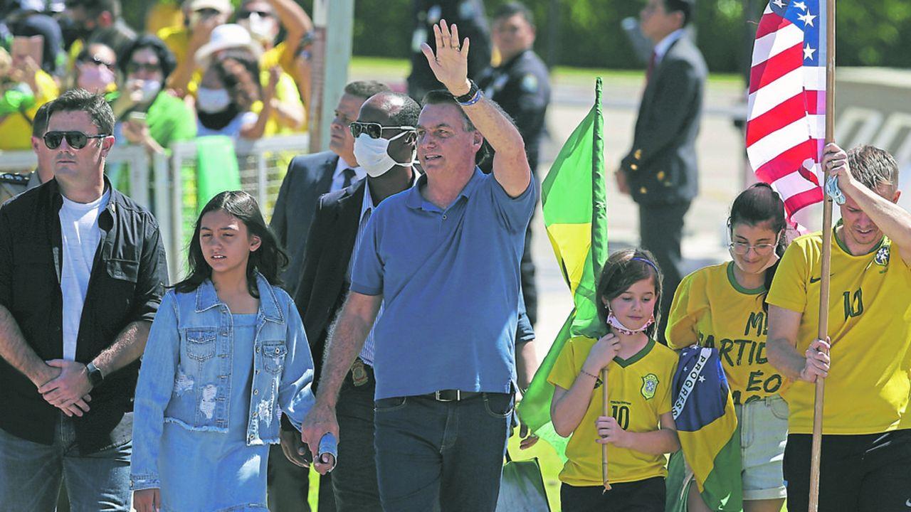 Le président brésilien Jair Bolsonaro tient la main de sa fille et salue des supporters qui manifestent contre son ancien ministre de la Justice, Sergio Moro.