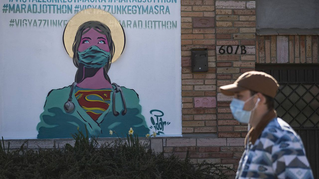 Un homme portant un masque de protection contre le coronavirus Covid-19 passe devant un graffiti portant l'inscription « restez chez vous et prenez soin les uns des autres » à Erd, au sud de Budapest (Hongrie), le vendredi 10 avril 2020.
