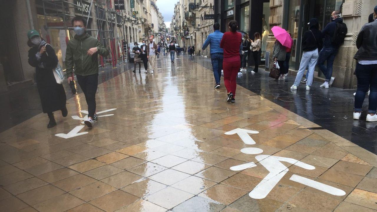 La mairie a imposé un marquage au sol contre les bousculades: au centre de la chaussée deux flèches matérialisent les deux sens de circulation. Les côtés sont réservés aux clients faisant la queue pour entrer dans les magasins.