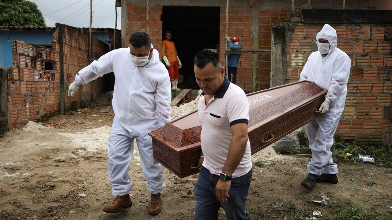 Un cercueil est transporté hors d'une maison à Manaus par un parent de la personne décédée et des employés d'un service funéraire.