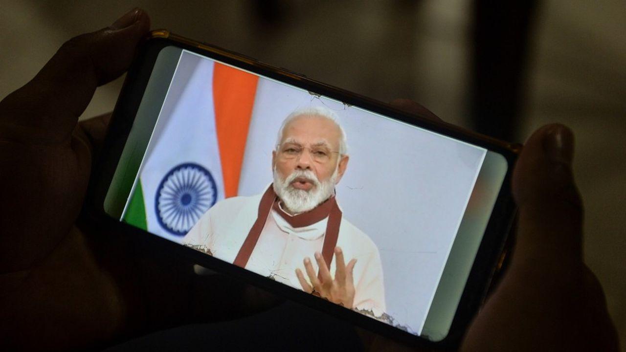 Un jeune suit l'intervention du premier ministre Narendra Modi sur sontéléphone mobile le 12mai 2020.