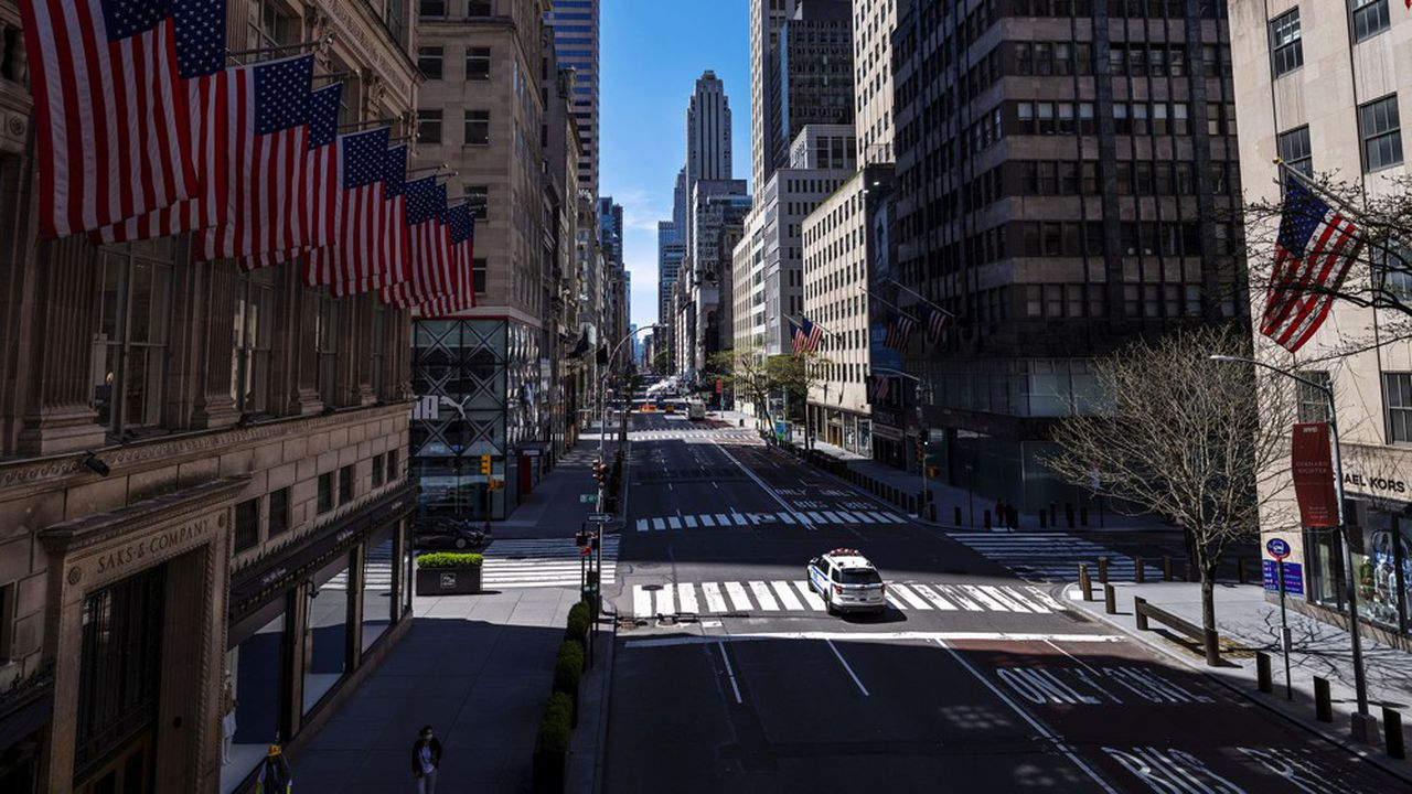 Une voiture de police longe la cinquième avenue déserte à New York, passant devant le magasin Saks. Une photo qui date du 5mai 2020.