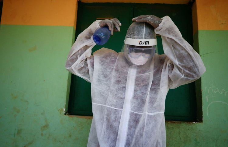 Un travailleur social pulvérise un spray sur sa protection durant un exercice lié au Covid-19 à Abuja,le 16 avril 2020