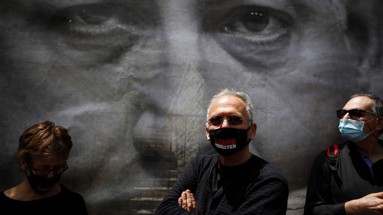 Un manifestant portant un masque 'Crime Minister' devant une photo de Benjamin Netanyahu, juste avant l'ouverture de son procès.
