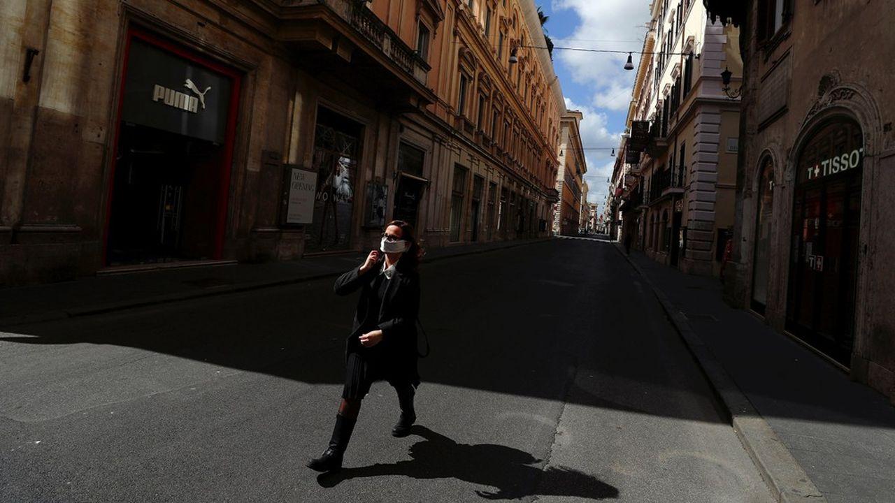 Une femme masquée marche dans les rues désertes de Rome, fin avril. Le confinement a fragilisé beaucoup de commerces qui connaissent des problèmes financiers et en font des proies faciles pour la mafia.