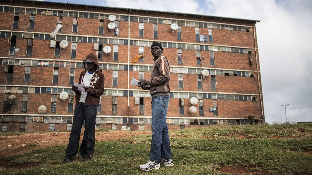 Des habitants du township d'Alexandra, dans la banlieue de Johannesbourg distribuent des tracts d'information sur le covid-19.