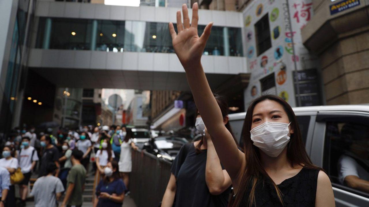 Une manifestante à Hong Kong proteste, le 27mai 2020, dans un geste affichant les cinq doigts de la main pour rappeler les «cinq demandes, pas moins» faites à l'exécutif.