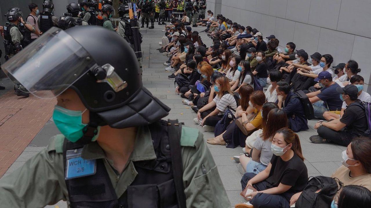 La police surveille des manifestants pro-démocratie arrêtés dans le Central district de Hong Kong, le 27mai 2020, alors qu'est examiné un projet de loi criminalisant tout outrage à l'hymne national chinois.