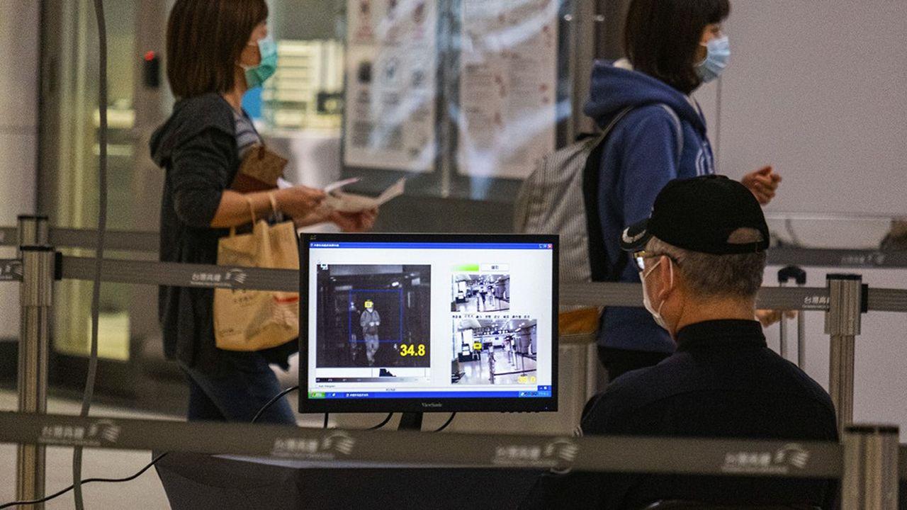 Un employé de la Taiwan High-Speed Rail (THSR) vérifie la température des utilisateurs avec un scanner thermique, Taipei, Taiwan, le 2 avril 2020.
