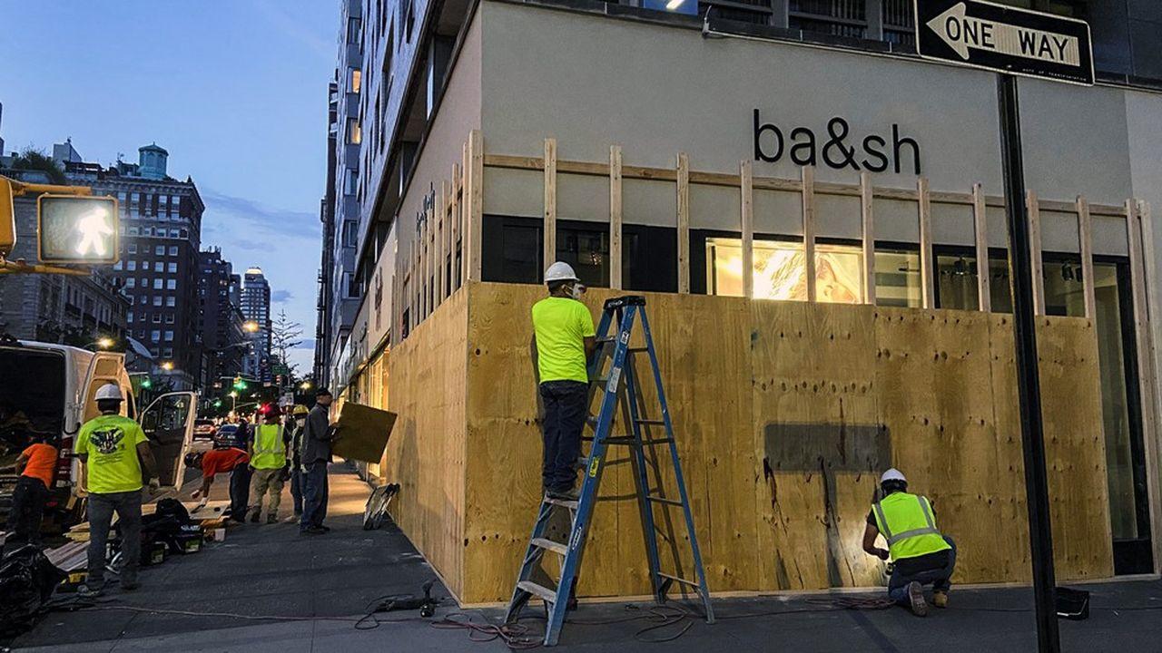 Lundi soir sur Madison Avenue dans Manhattan (New York), les grandes enseignes protégeaient à la hâte leurs vitrines.
