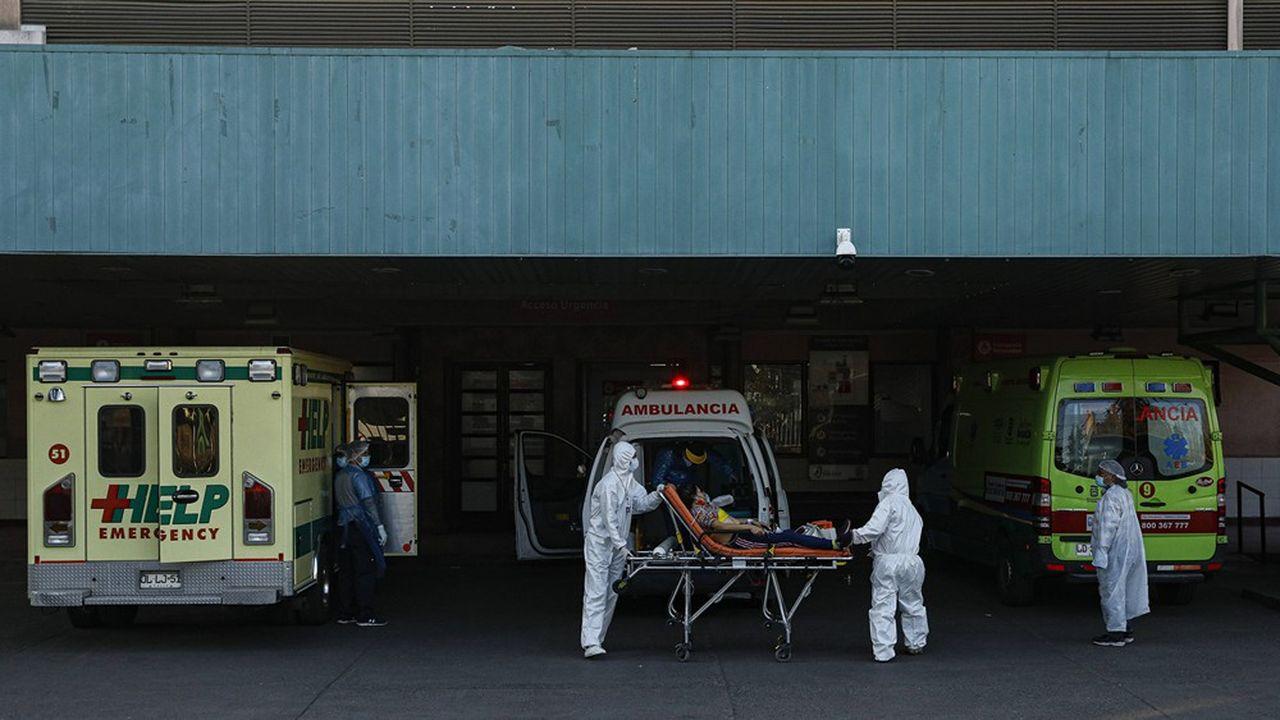 Un patient en détresse respiratoire est sorti d'une ambulance pour se faire admettre à l'hôpital San Jose à Santiago.