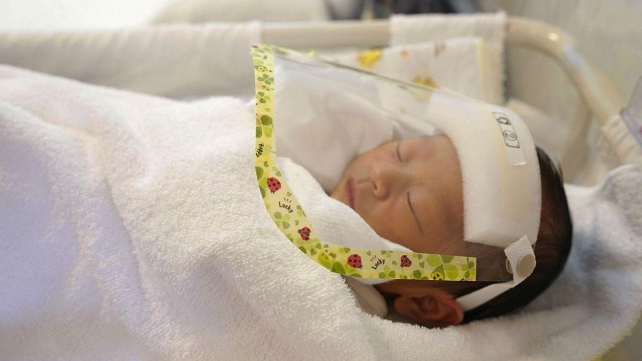 Un nouveau-né porte un masque de protection dans une maternité de Tokyo pour le protéger du coronavirus.